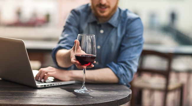 White man with beard at laptop holding a glass of wine